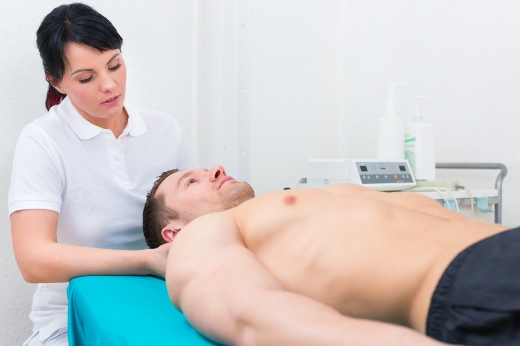 Patient at the physiotherapy getting medical massage from therapist