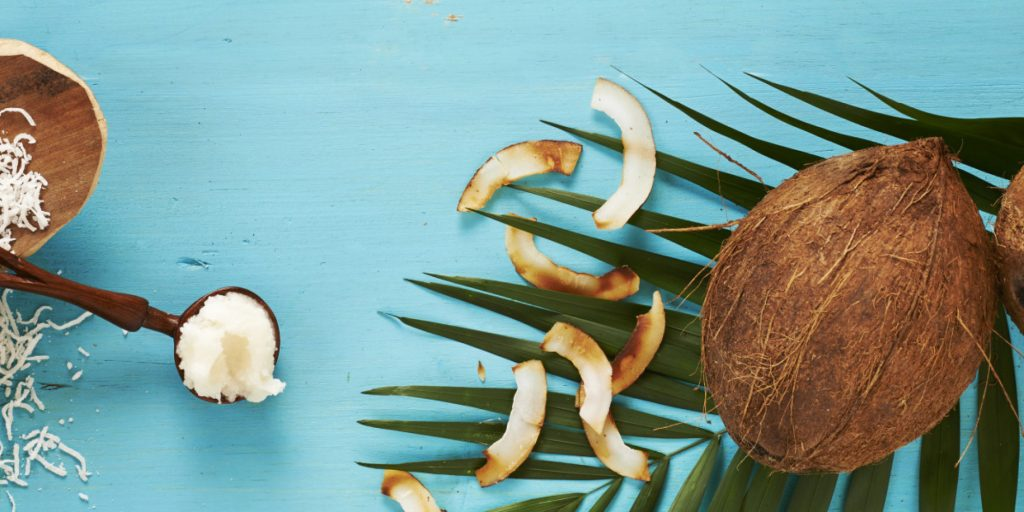 Coconut milk, whole coconuts, coconut oil, and toasted coconut, studio shot on turquoise background